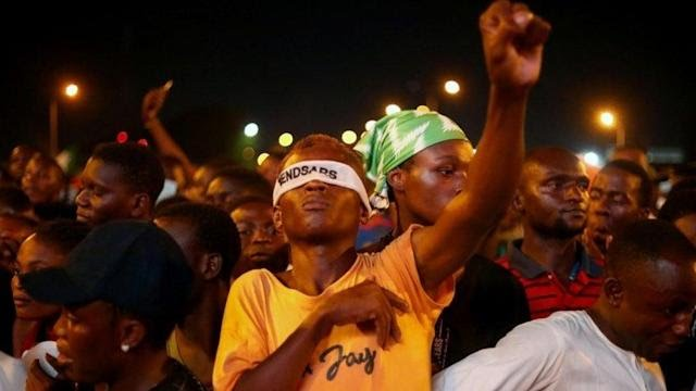 """A demonstrator wearing a blindfold with an inscription """"End Sars"""", gestures during protest against alleged police brutality in Lagos, Nigeria October 17, 2020"""