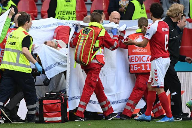 TOPSHOT - Medics stretcher Denmark's midfielder Christian Eriksen off the pitch after he collapsed during the UEFA EURO 2020 Group B football match between Denmark and Finland at the Parken Stadium in Copenhagen on June 12, 2021. (Photo by Jonathan NACKSTRAND / POOL / AFP) (Photo by JONATHAN NACKSTRAND/POOL/AFP via Getty Images)
