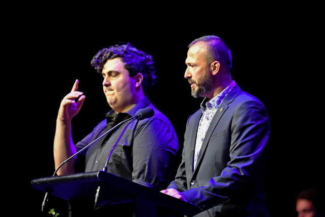 In this photo provided by the Department of Internal Affairs, Temel Atacocugu, right, who survived being shot nine times during the March 15, 2019, attack on the Al Noor mosque, speaks at a National Remembrance Service, Saturday, March 13, 2021, in Christchurch, New Zealand. Atacocugu said the slaughter was caused by racism and ignorance. The service marks the second anniversary of a shooting massacre in which 51 worshippers were killed at two Christchurch mosques by a white supremacist. (Mark Tantrum/Department of Internal Affairs via AP)