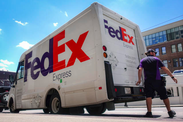 A FedEx delivery truck is loaded by an employee on the street, Tuesday, June 25, 2019, in downtown Cincinnati. FedEx Corp. (FDX) on Tuesday reported a fiscal fourth-quarter loss of $1.97 billion, after reporting a profit in the same period a year earlier. (AP Photo/John Minchillo)