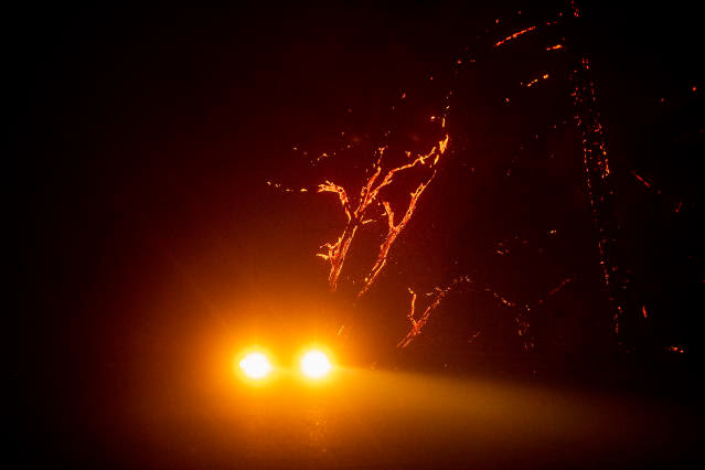 A car passes burning trees on Geysers Rd. as the Kincade Fire tears through unincorporated Sonoma County, Calif., on Thursday, Oct. 24, 2019. (Photo: Noah Berger/AP)