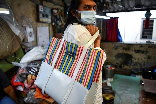 Founder of 'Chamar Studio', Sudheer Rajbhar poses as he shows his bags made from recycled rubber
