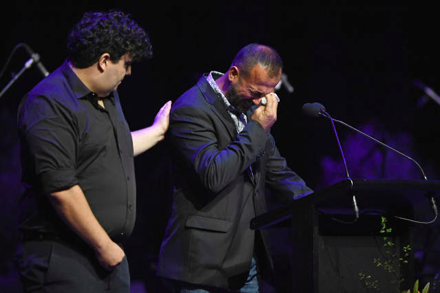 Temel Atacocugu, right, who survived being shot nine times during the attack on the Al Noor mosque, cries as he speaks at a National Remembrance Service, Saturday, March 13, 2021, in Christchurch, New Zealand. The service marks the second anniversary of a shooting massacre in which 51 worshippers were killed at two Christchurch mosques by a white supremacist. (Kai Schwoerer/Pool via AP)