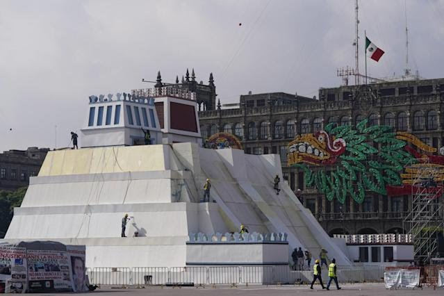 A replica of an Aztec temple near an image of a plumed serpent in red, orange and green on buildings
