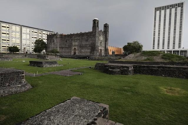 """An ancient Aztec temple, foreground, a Spanish colonial church, top center, apartments, top left, and a modern government office constructed in the 1960s, right, stand in the Plaza of Three Cultures in Mexico City, Tuesday, May 18, 2021. The plaza honors Indigenous Mexico, Spanish colonialism and the """"modern"""" mixed-race Mexico that resulted from the conquest 500 years ago. (AP Photo/Eduardo Verdugo)"""