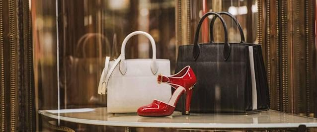 Two designer bags and a pair of shoes sit on a table in a shop.