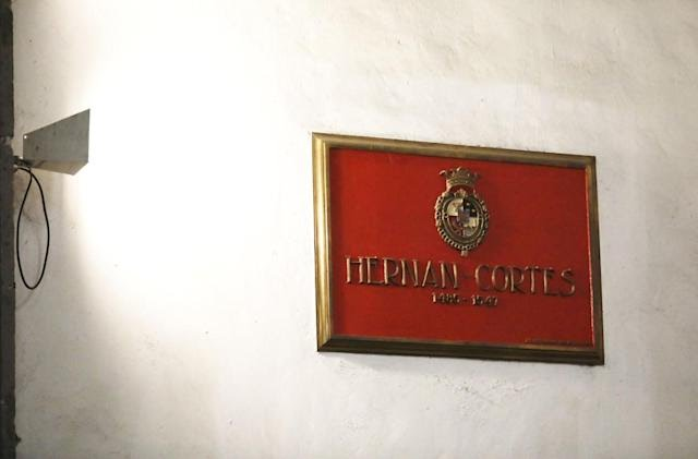 A red plaque with a gold frame bears the words, also in gold, HERNAN CORTES: 1485-1547