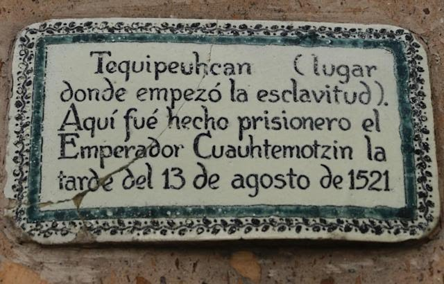 A plaque with a green and black border with black letters in Spanish against a white background